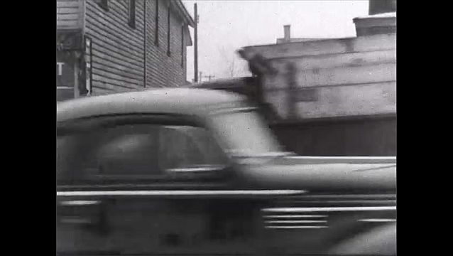 1940s: For Rent sign in window. Man walks down street. Cars on street. Truck turns on to side street. View of factory roof.