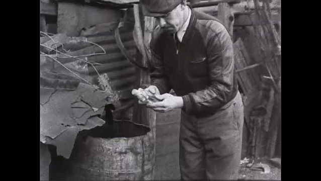 1940s: Man picks items out of barrel. Woman dumps out basket into pile of garbage.