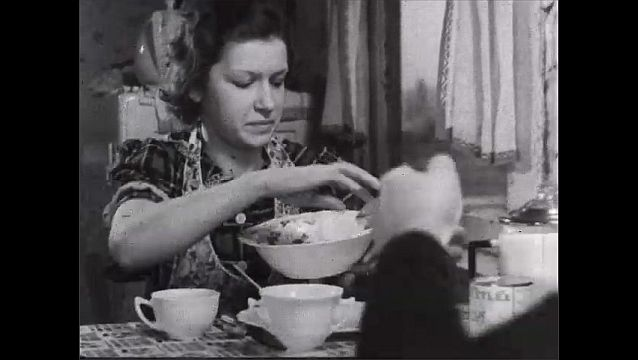 1940s: Man passes bowl to woman, who spoons food onto her plate.