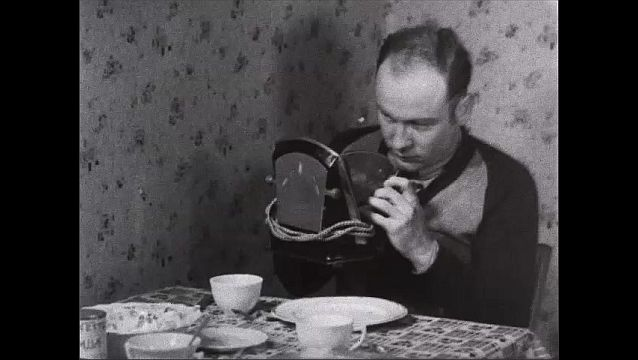 1940s: Man picks up appliance and puts it down.
