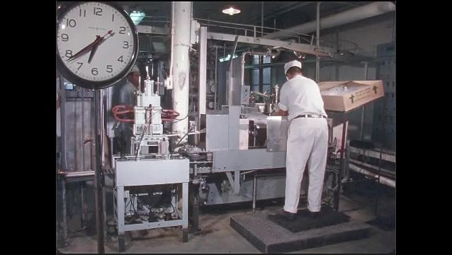 1960s: UNITED STATES: worker labels box on conveyor. Man takes box off conveyor.