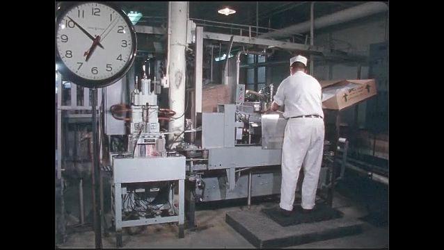 1960s: UNITED STATES: Scene 1, Take 5 slate. Man handles boxes in factory. Man slide box along conveyor.