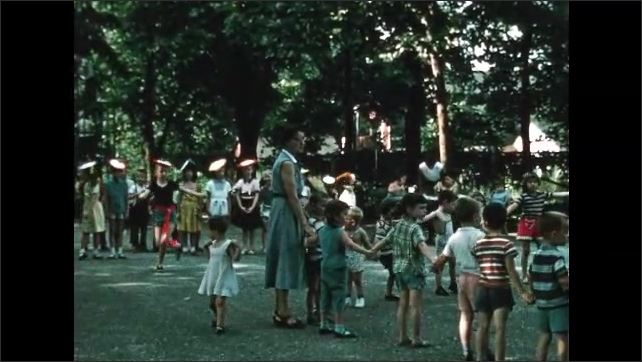 1960s: Girl dances with friends on playground. Children play at daycare playground. Women watch children play near daycare building.