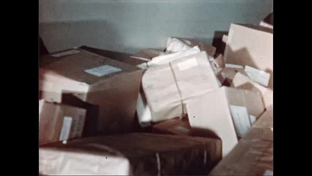 1950s:Brown paper packages travel on a conveyor belt system.