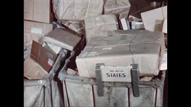 1950s: Postal workers sort large pile of brown paper packages, tossing them into canvas carts. Worker moves cart away.