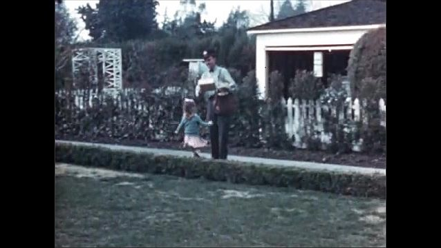 1950s:Canvas mail bags are unloaded from train car. Little girl swings in her yard, sees mailman, and little girl runs up to mailman. Mailman hands her a package. Little girl runs into house.