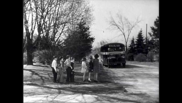 1940s: Truck drives down road.  Trucks in warehouse parking lot.  School bus picks up children.  Bus driver speaks.