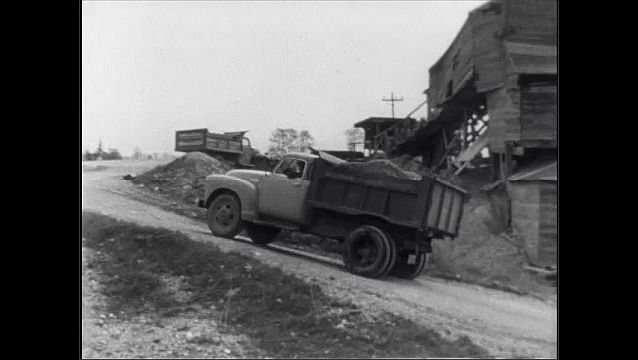 1940s: Truck drives up hill.  Men load parked truck.