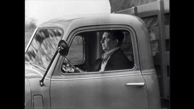 1940s: Firetruck zooms down street.  Man drives truck.
