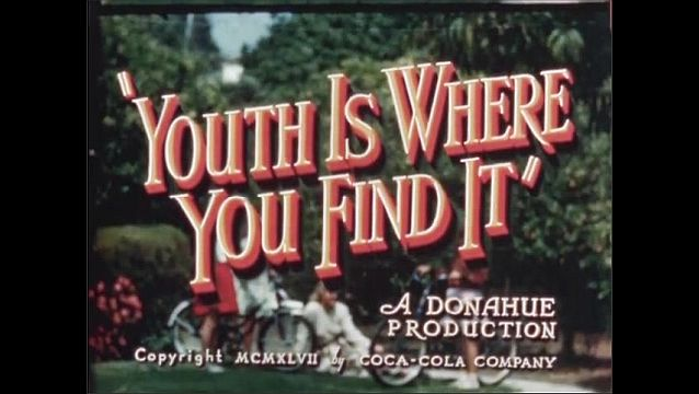 1940s: UNITED STATES: The Coca-Cola Company Presents. A Donahue Production. Boys stand in group. Police man talks to teens.