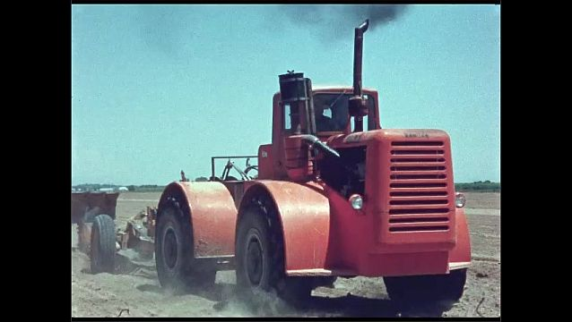 1960s: UNITED STATES: tractor and plough on farm land. Plough churns up soil in field. Dust around tractor trailer.
