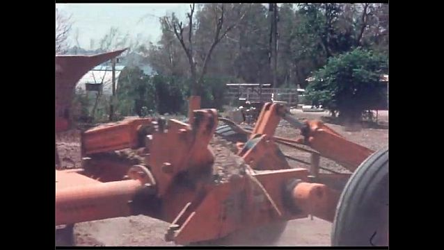 1960s: UNITED STATES: close up of plough attached to tractor. Tractor churns up soil in field. Wheel on trailer.
