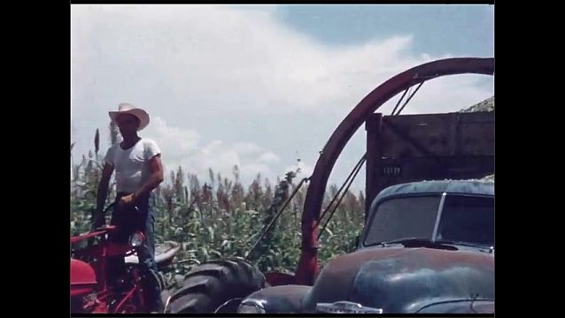 1960s: UNITED STATES: machine gathers harvest from field. Machine cuts down crops