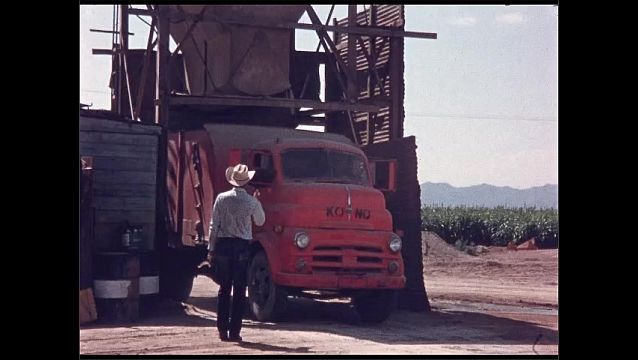 1960s: UNITED STATES: truck drives under chute. Finger presses switch on control panel