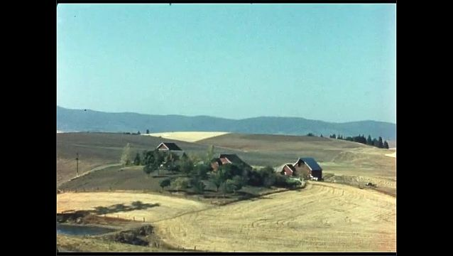 1960s: Large sprawl of farmland. Farmhouse. Man rides tractor across field.