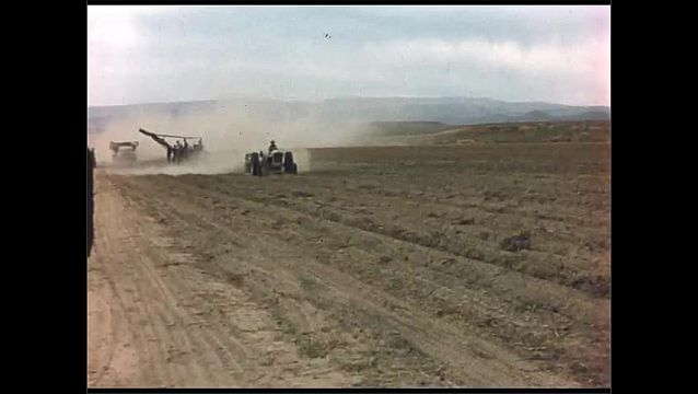 1960s: People working to harvest crops in field. Title card. Tractor plows across dirt field harvesting potatoes which get filled in truck following alongside.