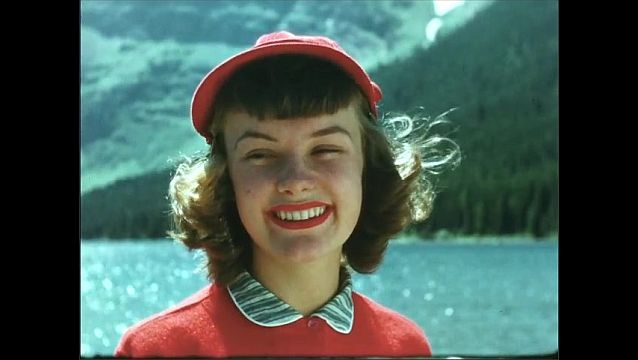 1950s: Woman stands outside, looks around, smiles, laughs, talks. Woman sits on boat on lake shore.