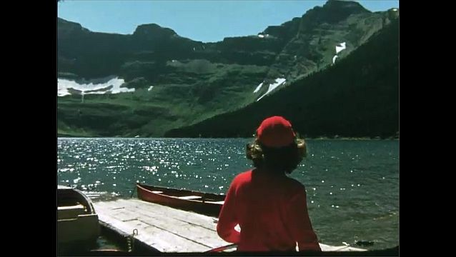 1950s: Woman sits on boat on lake shore, looks out at mountains and lake.