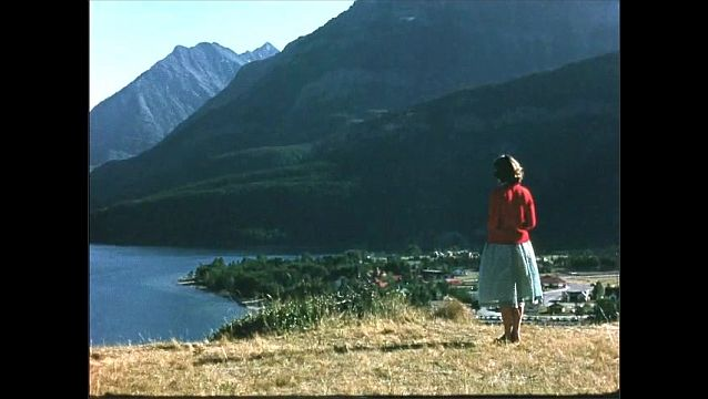 1950s: Woman stands in field in front of lake and mountains.