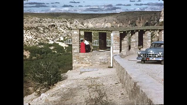 1950s: UNITED STATES: bridge across ravine. View along canyon. Car parked at viewing spot. Buildings in city. Street in city