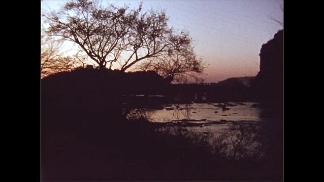 1950s: UNITED STATES: car drives through town. River and sunset. The End title
