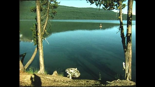 1950s: View of lake. Mountain reflected in lake.
