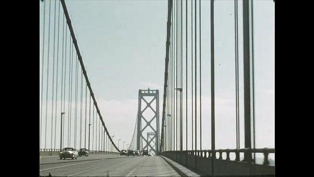 1950s: Driving across bridge. View of Alcatraz Island from San Francisco.