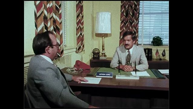 1970s: UNITED STATES: Private Industry Council logo. Men talk in office. Students work with engineering components