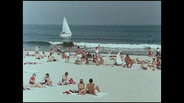 1970s: UNITED STATES: man plays golf on green. People on beach in sun. Man talks to board. Lake and trees.