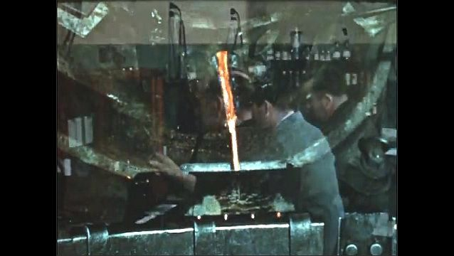 1950s: Factory.  Man turns wheel to pour molten metal into mold.  Man puts pieces of silver into beaker.