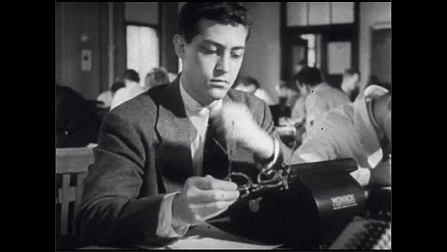 1950s: UNITED STATES: man with glasses studies in library. Medical student studies in library. Statistics laboratory. Man arrives at university