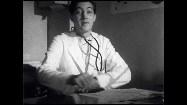 1950s: UNITED STATES: doctor lifts patient to floor. Doctor looks at case history in file. Doctor sits at desk.