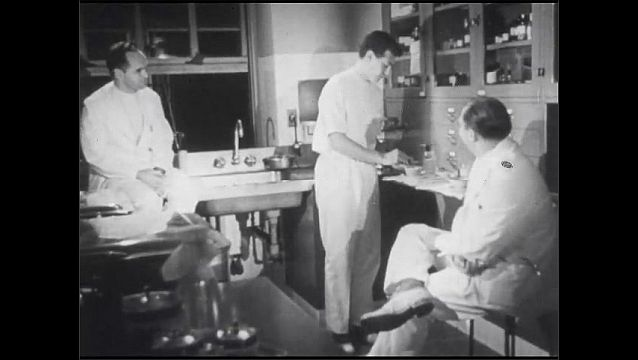 1950s: UNITED STATES: doctor talks with parents. Doctors have coffee in room after rounds. Resident talks to colleagues