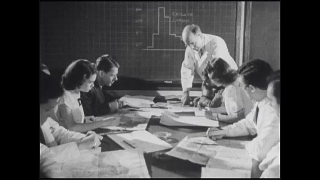 1950s: Four men and woman stand looking at large hospital building. People sit around table as man stands pointing at chalk board of information. Blueprint with pinpoints in it.