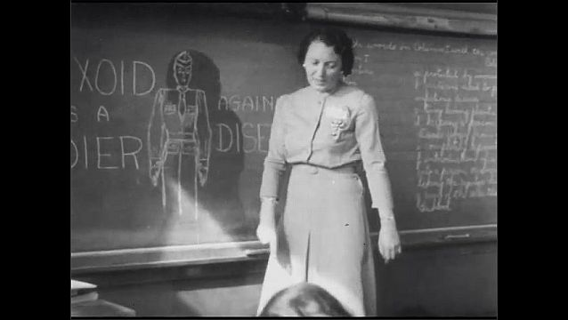 1950s: Man stands talking to women seated around table. Woman stands in front of classroom teaching. Children raise hands. Sign about diphtheria prevention.