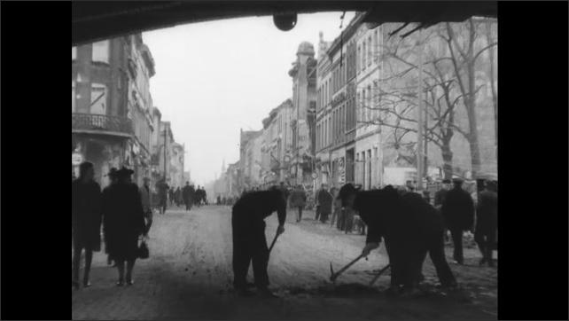 1940s Germany: Writing on clapboard. People walking in street, men working on road.
