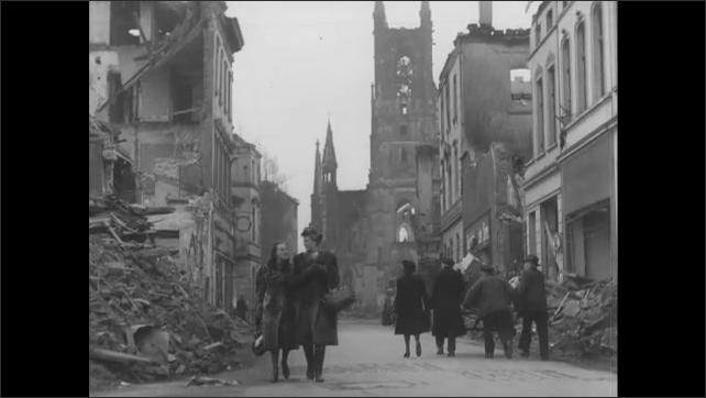 1940s Germany: People walking on road by wreckage, women walk past camera.