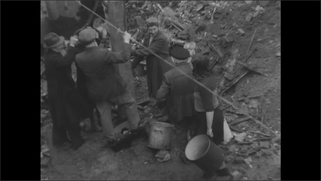 1940s Germany: High angle, woman walks into pit with buckets, walks to people by well. Woman pumping well.