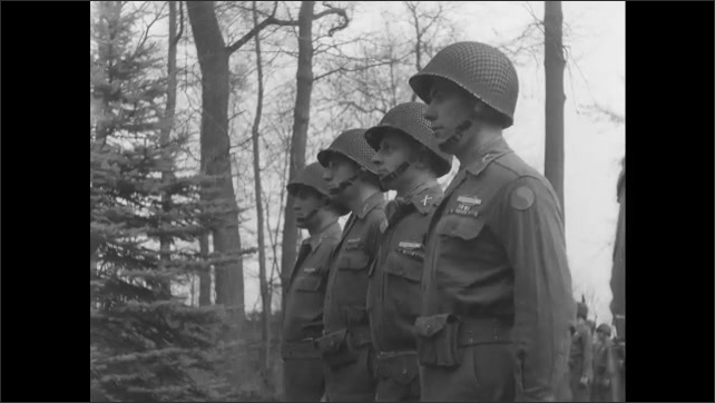 1940s Germany: Soldier reading from paper. Soldiers standing in formation. Line of soldiers. Panning shot of soldiers.