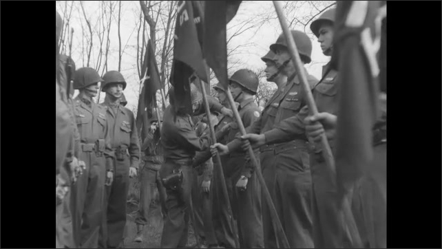 1940s Germany: Soldiers standing with flags, officer talking, pins medal on soldier. Officer pins medal, talks to soldier.