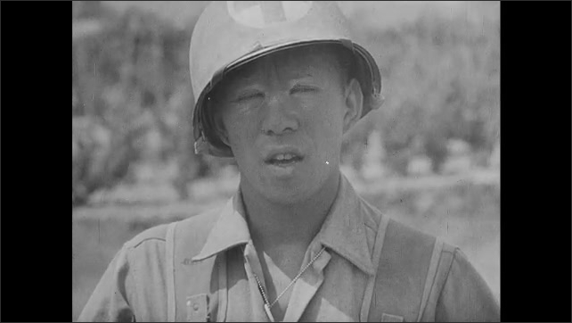 1940s: Japanese American soldier speaks. Group of soldiers sit outside, eat, maintain equipment.