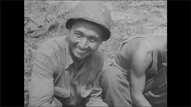 1940s: Group of Japanese American soldiers sit together outside. Soldiers cook and eat food, maintain equipment. Soldier sits with children, makes paper airplane.