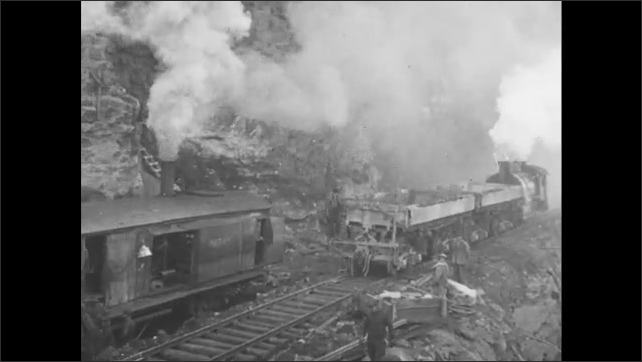 1910s: Men walk along railroad running through excavation site. Train car comes through on tracks and stops. Loader dumps dirt onto train car.