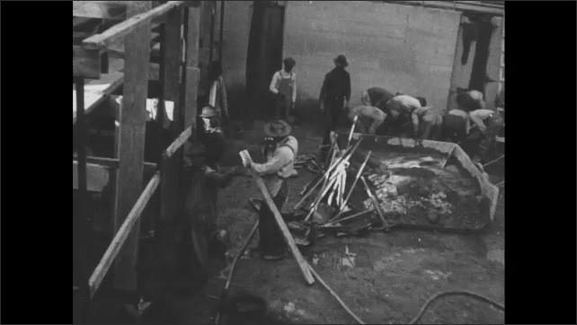 1910s: Men work construction foundation of building.