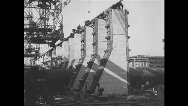 1910s: Large, industrial construction site. Large overhead crane moves down tracks on site.