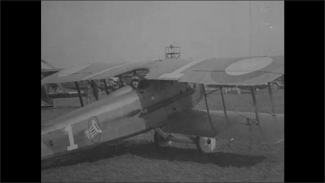 1910s: Plane taxis across airfield as men stand in foreground and watch. Pilot in cockpit of plane smiles, talks and gestures.