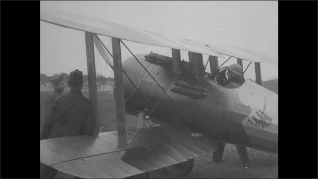 1910s: Plane takes off. Man spins propeller of plane. Pilot in cockpit of plane smiles.