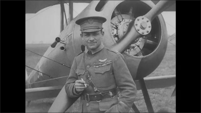 1910s: Man smokes cigarette with plane in background. Man speaks and smiles.