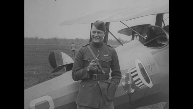 1910s: Man speaks and smiles while leaning against plane. Man puffs on pipe and smiles while leaning against plane.