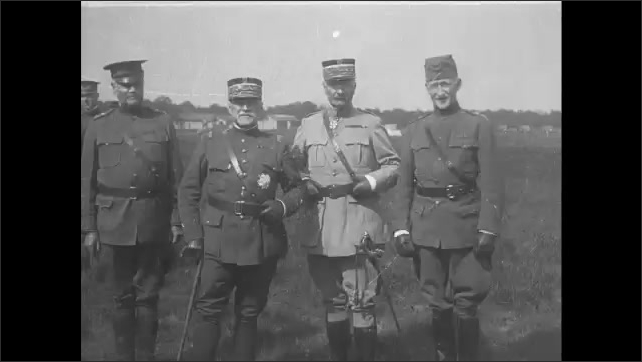1910s: French general salutes troops. Soldiers march past biplanes and hangars on base. French and American generals pose in field.